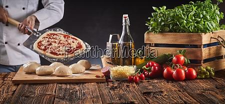 chef en una pizzeria preparando una