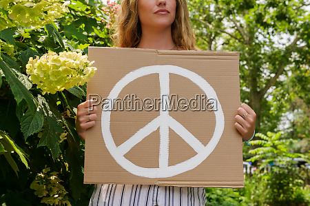 mujer sosteniendo simbolo de paz por