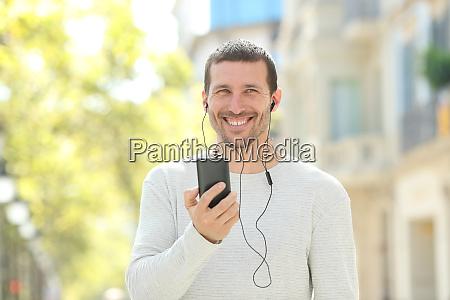 hombre adulto feliz escuchando musica mirando