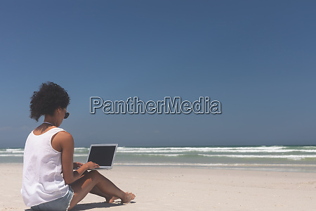 young woman using laptop at beach