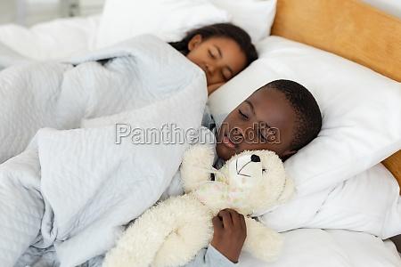 hermanos durmiendo juntos en la cama