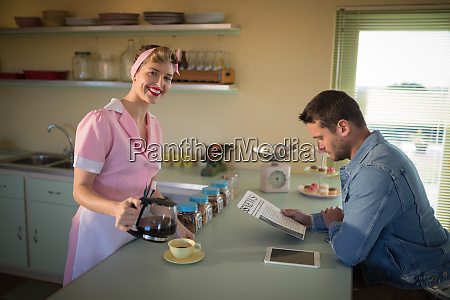 waitress serving black coffee while man