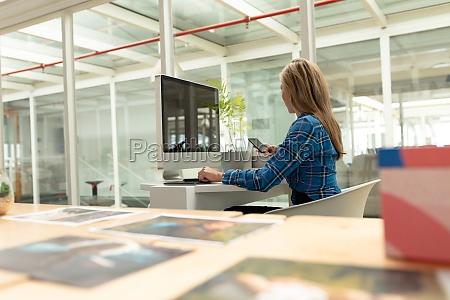 disenyadora grafica femenina usando telefono movil