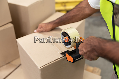 male worker packing cardboard box with