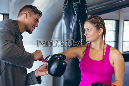 male trainer helping female athletic to