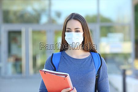 estudiante con una mascara caminando en