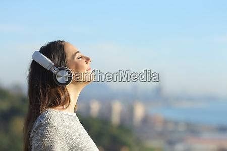 mujer escuchando musica respirando al aire