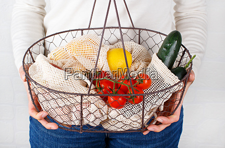 woman keeps backet with fresh vegetables
