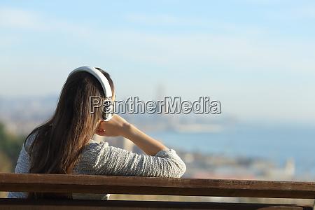 mujer relajada escuchando musica contemplando vistas