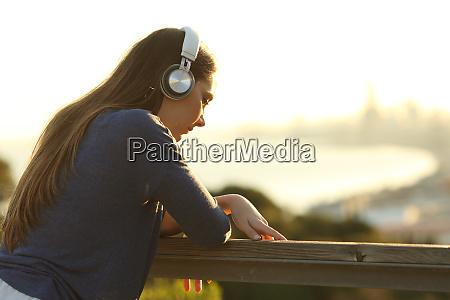 chica triste escuchando musica mirando hacia