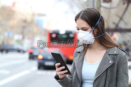 mujer con mascara usando el telefono