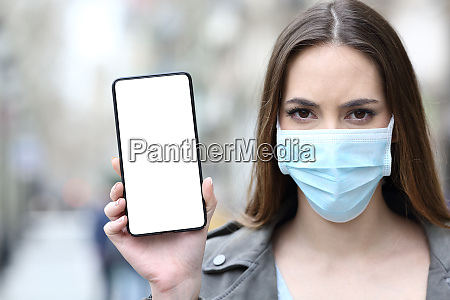 woman with protective mask showing phone