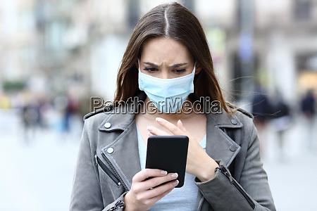 chica asustada con mascara leyendo noticias