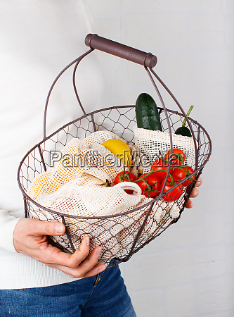 woman keeps backet with vegetables and