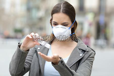 chica con mascara aplicando desinfectante de
