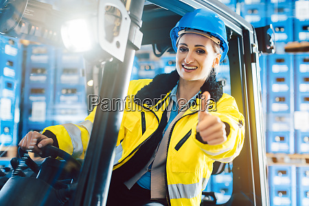worker woman showing thumbs up in