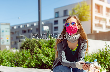 mujer con mascara facial sentada afuera