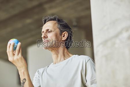 hombre mayor sosteniendo mini globo en