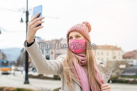 mujer con mascara corona haciendo selfie