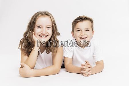 lindos hermanos sonrientes acostados sobre fondo