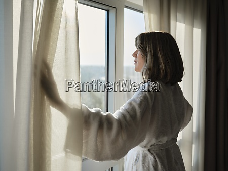 mujer rubia mayor abriendo cortina blanca