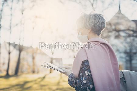 senyora mayor con mascara facial leyendo