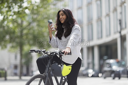 mujer en bicicleta usando telefono inteligente